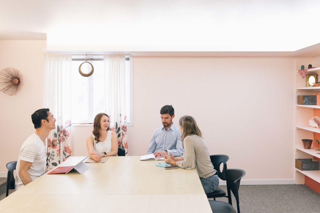 Photo of four people sitting around a conference table inside the Cohere conference room. The walls are light pink and everyone is smiling and laughing.