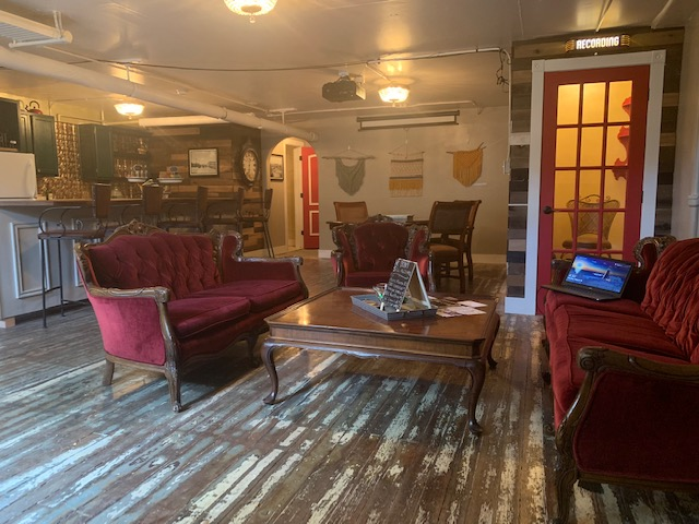 Photo of the space, which shows the bar with bar stools and another area with maroon velvet couches. Floor is distressed hardwood.