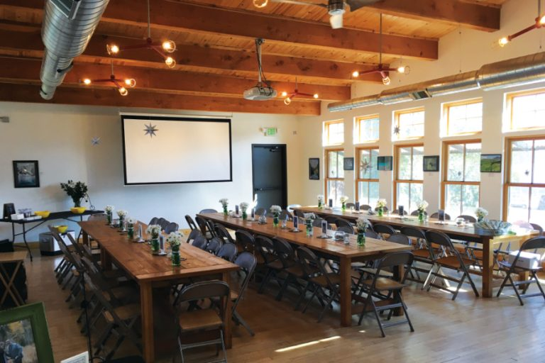 Photo of the upstairs event venue set up with long tables for seating, flower vases on the tables, a projector screen, exposed beams and HVAC and many windows.
